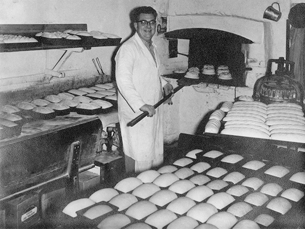 Cyril Beckett putting loaves in the oven