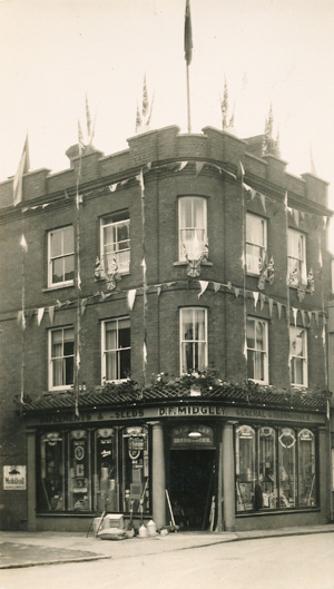 Black and white photo of the shop front decorated with flags